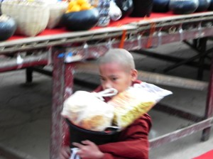 Young monk receiving offerings at Ananda Temple